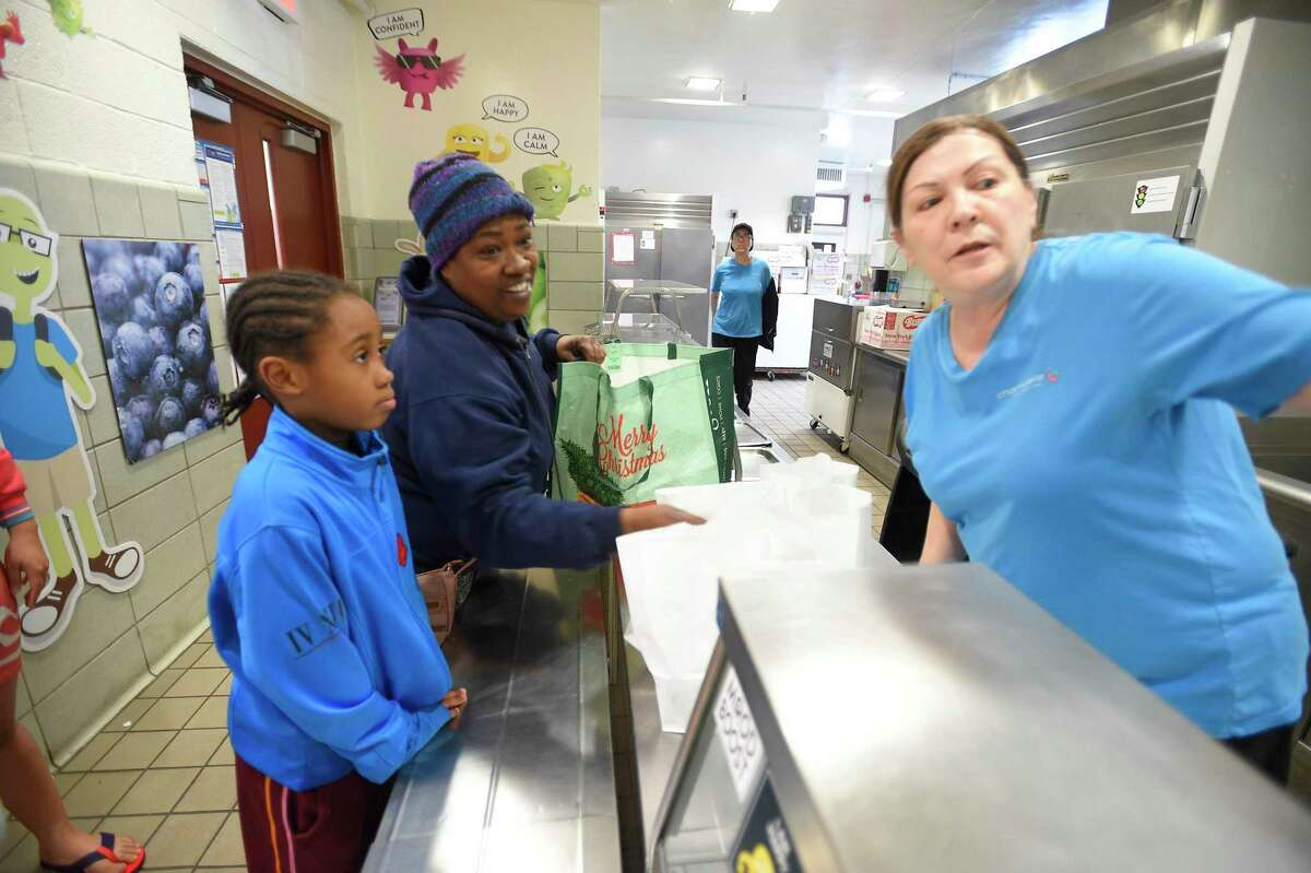 Miriam Roldan, coordinator of the food services at K.T. Murphy School directs Sharon Waddell and her child Adelynn Beau, 8, a third grader at the school, on where to pick up cartons of milk that go along with a bag lunch they received on March 13, 2020 as part of the Grab and Go lunch program that has been set up for the duration of the school closings in response the the COVID-19 crisis in Stamford, Connecticut.