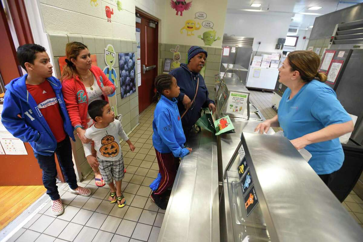 Miriam Roldan, coordinator of the food services at K.T. Murphy School works with families picking up a bag lunch on March 13, 2020 as part of the Grab and Go lunch program that has been set up for the duration of the school closings in response the the COVID-19 crisis in Stamford, Connecticut.