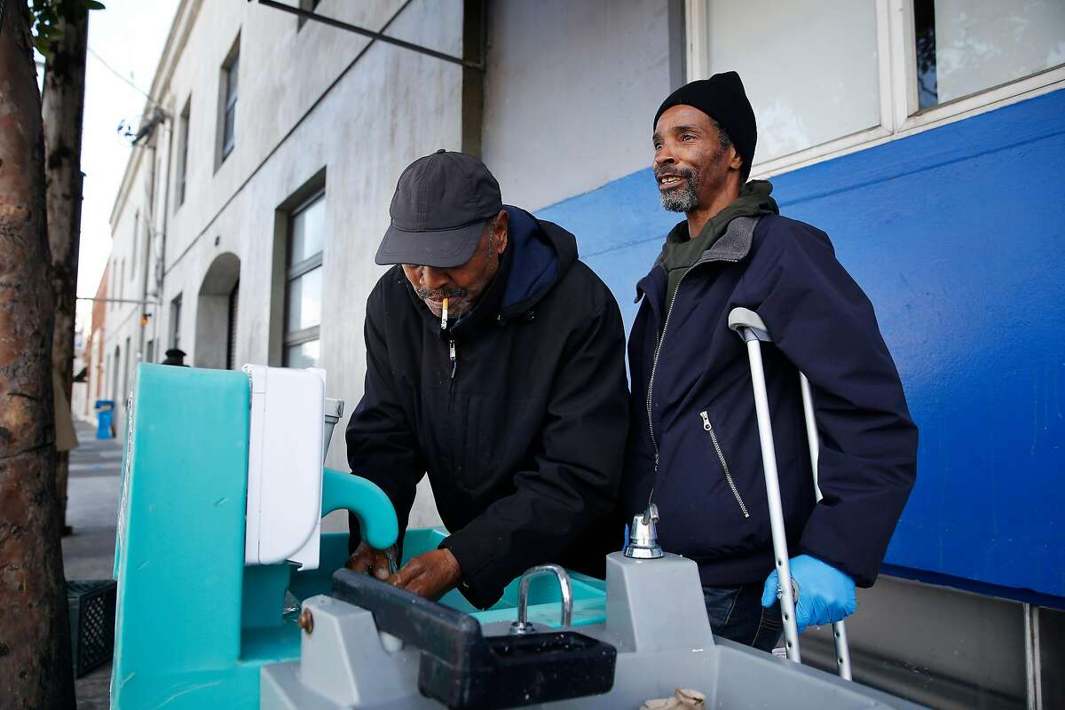 Brian Hayes (right) uses a foot pedal to pump water from a tap to help Hanna Wallace (left) wash his hands at a hand washing station outside of Multi-Service Center South on Thursday, March 19, 2020 in San Francisco, Calif.
