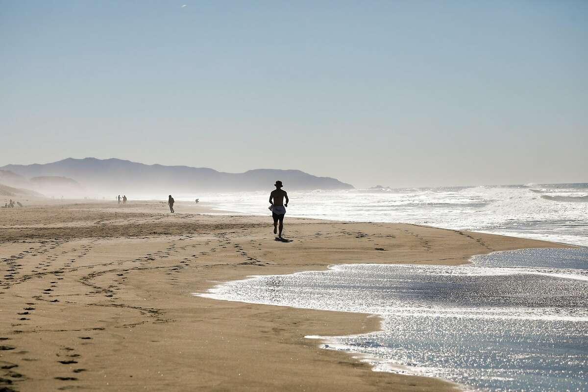 A man runs on Ocean Beach on a sunny day last month in San Francisco.