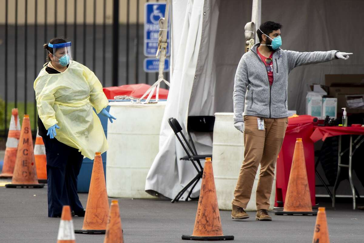 Health officials at a Verily coronavirus drive-thru test clinic wait for patients to instruct and verify before directing them inside the San Mateo County Event Center, Tuesday, March 17, 2020, in San Mateo, Calif.