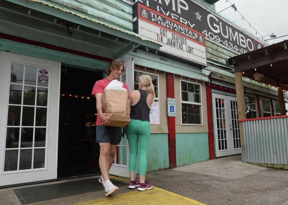 Maddie Allen holds the door for Tripp Daleo as they and Katherine McAlee (not pictured) carry out their to-go order at the Tia Juanita's Fish Camp in Beaumont on the first day of area restaurant and bar closures.  Photo taken Thursday, March 19, 2020 Kim Brent/The Enterprise Photo: Kim Brent / The Enterprise / BEN