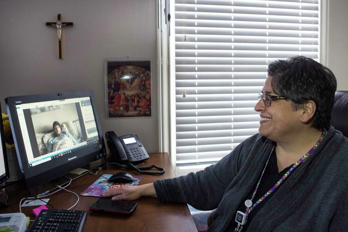 Dawn Malone, a lay chaplain for the archdiocese of Galveston-Houston, ministers to cancer patient Austin Bond, via video conference on Thursday, March 19, 2020 in Houston. Coronavirus has limited local chaplains the ability to minister to the sick or elderly. Chaplains have also been told not to minister to any group more than 10.