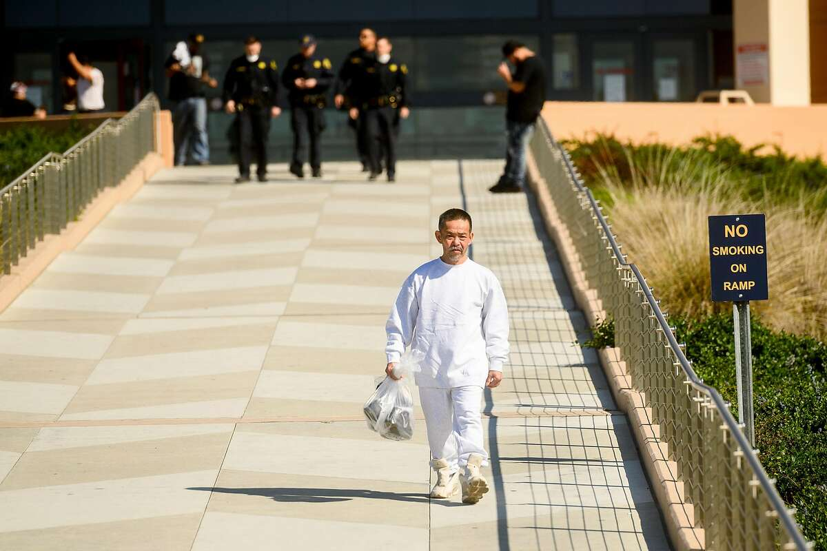 I Vuai carries his belongings as he leaves Santa Rita Jail on Friday, March 20, 2020, in Dublin, Calif. He was one of several hundred prisoners granted early release as the county tries to prevent coronavirus spread in a vulnerable population.