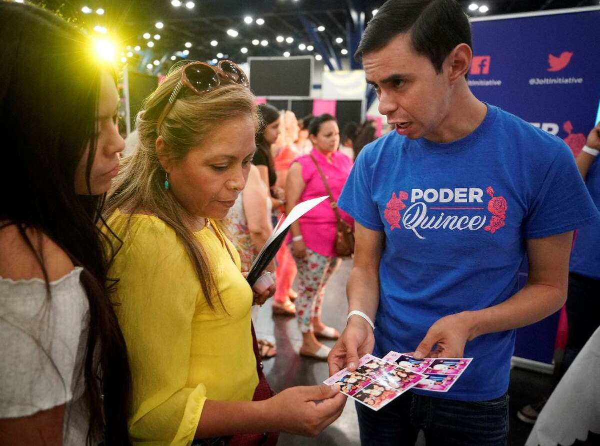 Julie Tovar, 16, and her mother, Carina Tovar, talk with Antonio Arellano, interim excutive director, right, at the Poder Quince booth during the Quince Expo at the George R. Brown Convention Center Sunday, Aug. 4, 2019, in Houston. Poder Quince is a voter registration drive by Jolt Initiative to increase Latino voter turnout. The group provides a free photobooth at the quinceañera and conducts onsite voter registration during the party.