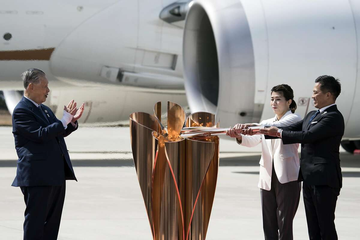 MATSUSHIMA, JAPAN - MARCH 20: Tokyo Olympic and Paralympic Organizing Committee President Yoshiro Mori (L) claps on as Olympic gold medalists Tadahiro Nomura (R) and Saori Yoshida (C) light the Olympic flame during the Tokyo 2020 Olympic Games Torch Arrival Ceremony at the Japan Air Self-Defense Force Matsushima Air Base on March 20, 2020 in Matsushima, Miyagi, Japan. (Photo by Tomohiro Ohsumi/Getty Images)
