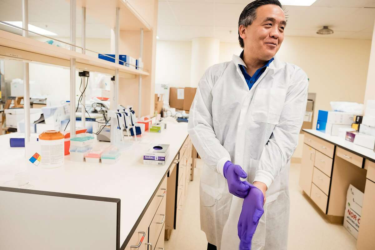 Microbiologist Dr. Charles Chiu dons gloves at a new lab that will test and sequence the genomes of COVID-19 samples in San Francisco, Calif. on Friday, March 20, 2020. The infectious disease specialist at UCSF is sequencing the genomes of every case of COVID-19 in the Bay Area that he can get his hands on.
