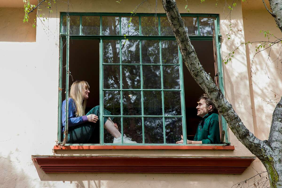 Samantha Dooley, 23, a copywriter for an ad agency and Liam Doran, 22, a UC Berkeley Grad Student studying Mechanical Engineering, pose for a portrait in the window of their home in Berkeley, Calif. Tuesday, March 17, 2020. Dooley is working from home as a result of the Coronavirus outbreak and Doran is working remotely to try and do as much as he can for his capstone project, although progress has been inhibited by the lack of access to campus machine shops and labs.