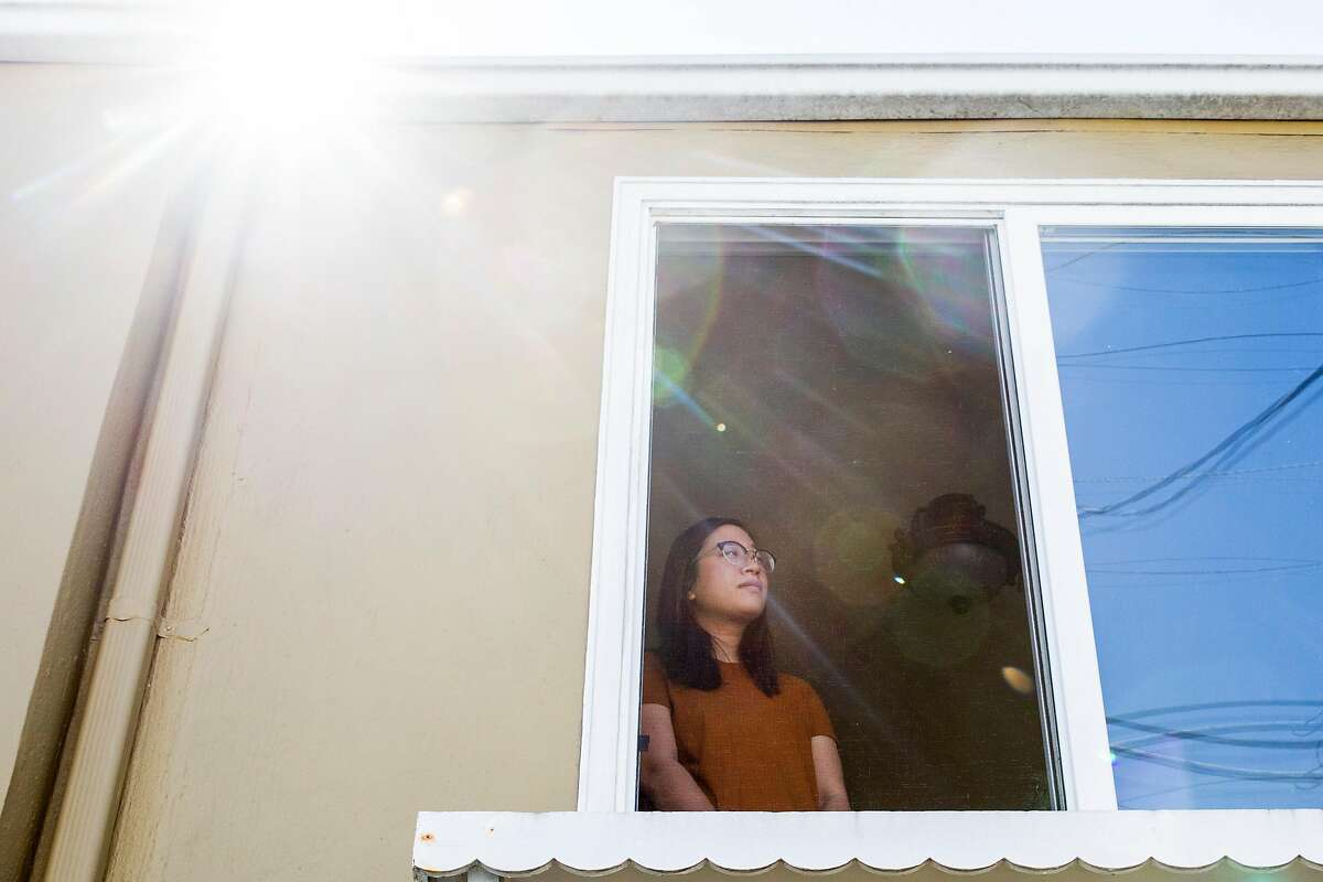 Tiffany Sun poses for a portrait in the window of her home in San Francisco, Calif. Friday, March 20, 2020.