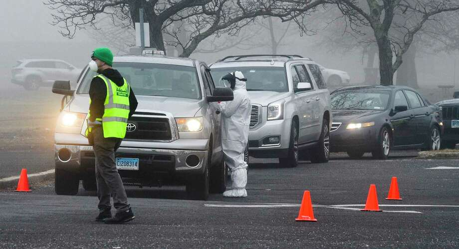 A line of cars wait as medical personnel from Murphy Medical Associates administer drive-thru screenings for the Covid-19 coronavirus at a mobile testing site set up at Cummings Beach in Stamford, Conn. , March 20, 2020. Photo: Matthew Brown / Hearst Connecticut Media / Stamford Advocate