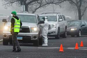 A line of cars wait as medical personnel from Murphy Medical Associates administer drive-thru screenings for the Covid-19 coronavirus at a mobile testing site set up at Cummings Beach in Stamford, Conn. , March 20, 2020.