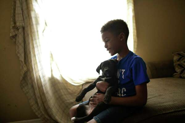 Marquese Jeffries-Johnson, 9, plays with the family's puppy on Wednesday. The family has no internet connection after being turned away by a Spectrum representative because it owes money from a previous connection. As schools switch to online learning, San Antonio's digital divide is widening.