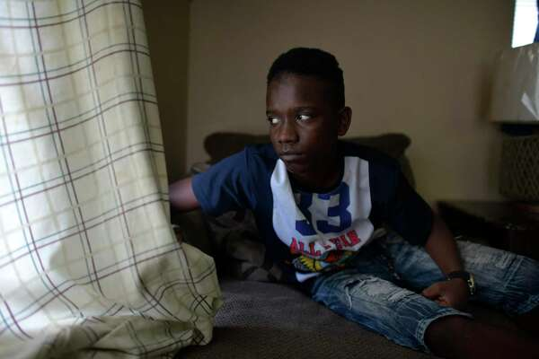 TaeChaun Jeffries, 15, looks out the window of his family's home on Wednesday. The four Jeffries Johnson children got laptops from their schools but the family can't get the free connection offered by Spectrum because their mother has a past due charge. As schools switch to online learning, San Antonio's digital divide is widening.