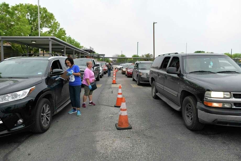 Arailia Jeffries and her son, Sancell, wait in the vehicle at right for a Chromebook to be loaned to them at Indian Creek Elementary School on Wednesday. Despite receiving the device, they have no internet connection at home to use it. As schools switch to online learning, San Antonio's digital divide is widening. Photo: Billy Calzada / ***MANDATORY CREDIT FOR PHOTOG AND SAN ANTONIO EXPRESS-NEWS /NO SALES/MAGS OUT/TV