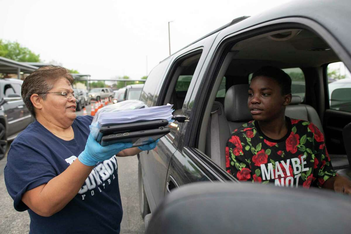 Maria Reyes of Indian Creek Middle School hands out Chromebooks in March 2020. Many students were unable to use the devices because they lack internet access. A recent survey found a fifth of Bexar County households don't have broadband connections.