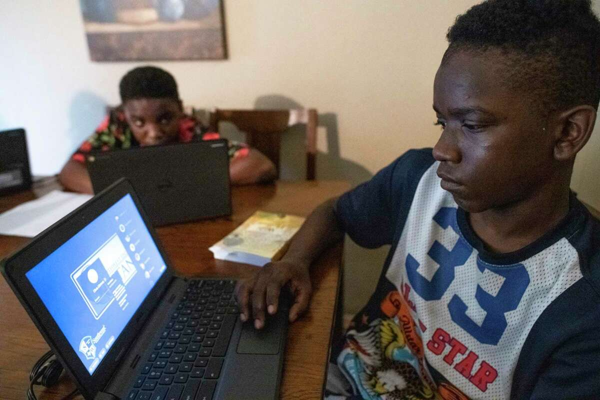 TaeChaun Jeffries Johnson, 15, and his brother, Sancell, 14 look over their Chromebook computers, loaned to them for home use during the coronavirus crisis by the Southwest Independent School District, on Thursday, March 19, 2020. The Jeffries Johnson children are unable to fully utilize the electronic devices for studying because they do not have an internet connection at homeTheir mother, Arailia Jeffries, was turned downed in her bid for the offered free internet by a Spectrum representative because she owes money from a previous connection.