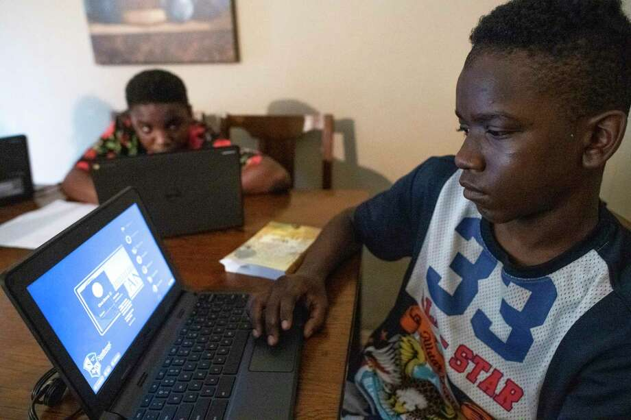 TaeChaun Jeffries, 15, and his brother, Sancell Jeffries-Johnson  14 look over their Chromebook computers Thursday. The devices were loaned to them for home use during the coronavirus crisis by the Southwest Independent School District, but the family has no internet connection. As schools switch to online learning, San Antonio's digital divide is widening. Photo: Billy Calzada /Billy Calzada / ***MANDATORY CREDIT FOR PHOTOG AND SAN ANTONIO EXPRESS-NEWS /NO SALES/MAGS OUT/TV