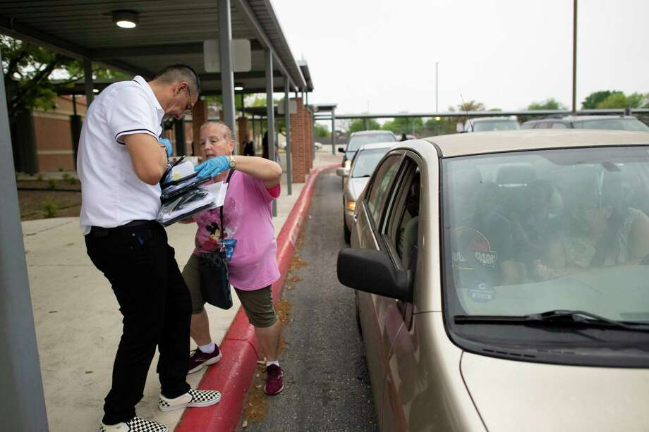 Reynaldo Piña and Angela Romanelli sort through Chromebooks to hand to students waiting in car lines at Indian Creek Elementary School on Thursday. As schools switch to online learning, San Antonio's digital divide is widening. Photo: Billy Calzada / ***MANDATORY CREDIT FOR PHOTOG AND SAN ANTONIO EXPRESS-NEWS /NO SALES/MAGS OUT/TV