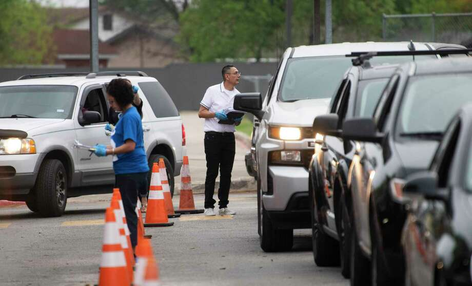 Reynaldo Piña, right, and other faculty and staff at Indian Creek Elementary School hand out Chromebooks to students as they wait in their cars Thursday. As schools switch to online learning, San Antonio's digital divide is widening. Photo: Billy Calzada / ***MANDATORY CREDIT FOR PHOTOG AND SAN ANTONIO EXPRESS-NEWS /NO SALES/MAGS OUT/TV