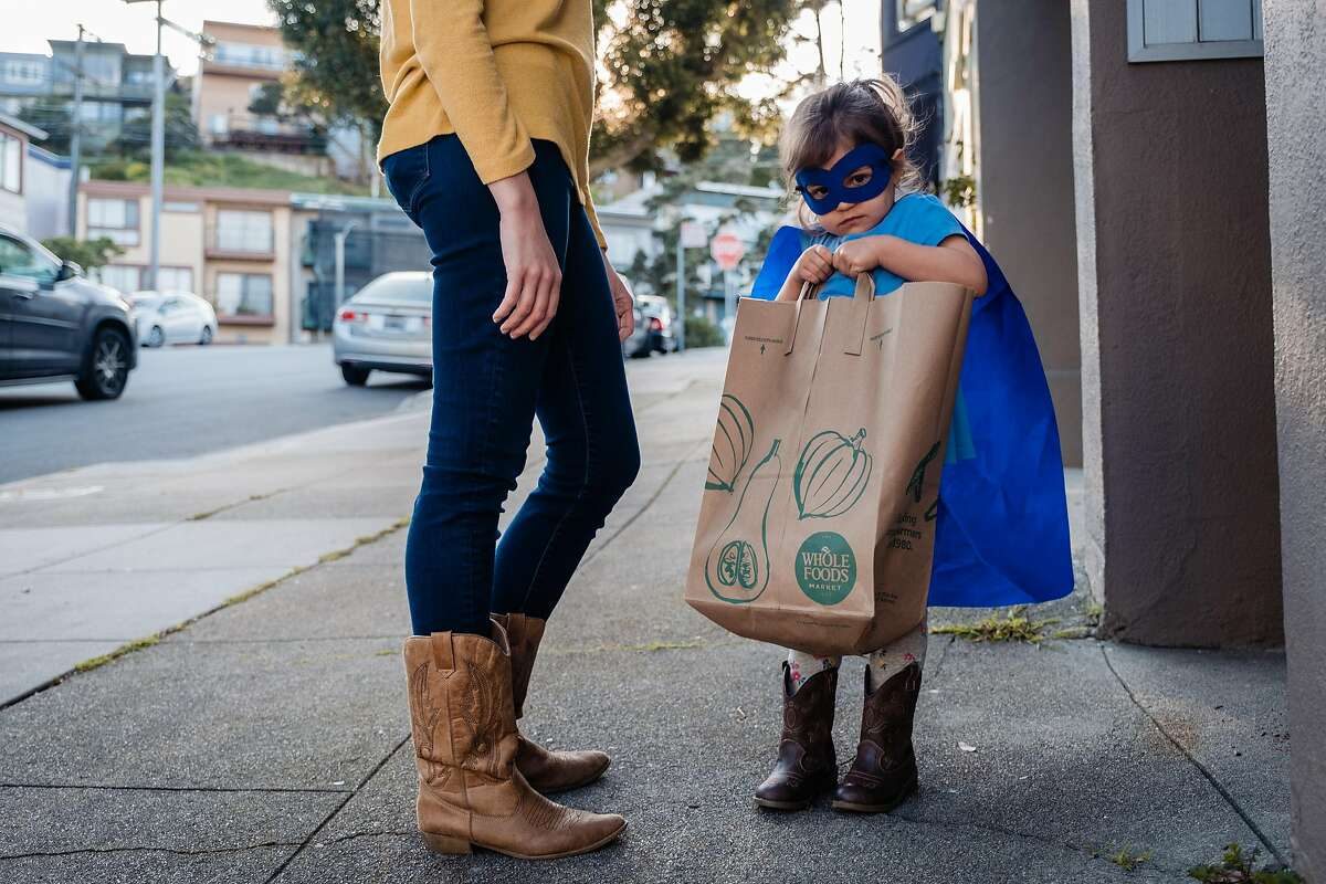 Jamiee Roesch and her daughter Finley deliver bags of donated masks, and gloves to a health care professional in San Francisco, Calif. on Thursday,