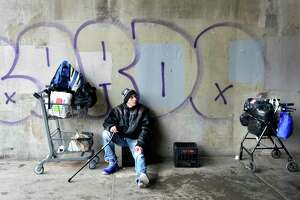 Shayne Buckley, homeless since he was released from prison in November 2019, sits under the Intertstate -91 bridge on Grand Avenue Ave. waiting for New Haven's Emergency Shelter to open its doors.