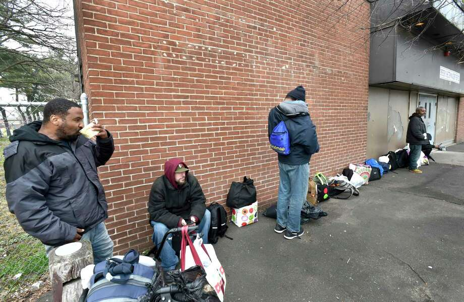 Homeless men Friday afternoon wait for  New Haven's Emergency Shelter on Grand Avenue to open its doors. Photo: Peter Hvizdak / Hearst Connecticut Media / New Haven Register