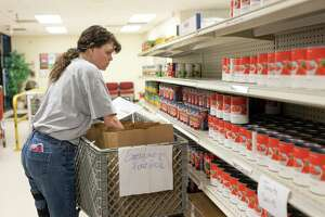 Northwest Assistance Ministries communications specialist, Shannel Vance, prepares an emergency day pack in the NAM's Watford Nutrition Center in Tomball, Friday, March 20, 2020. The food pantry has taken extra precautions in compliance with the Center of Disease Control and Preventions recommendations to stop the spread of COVID-19.