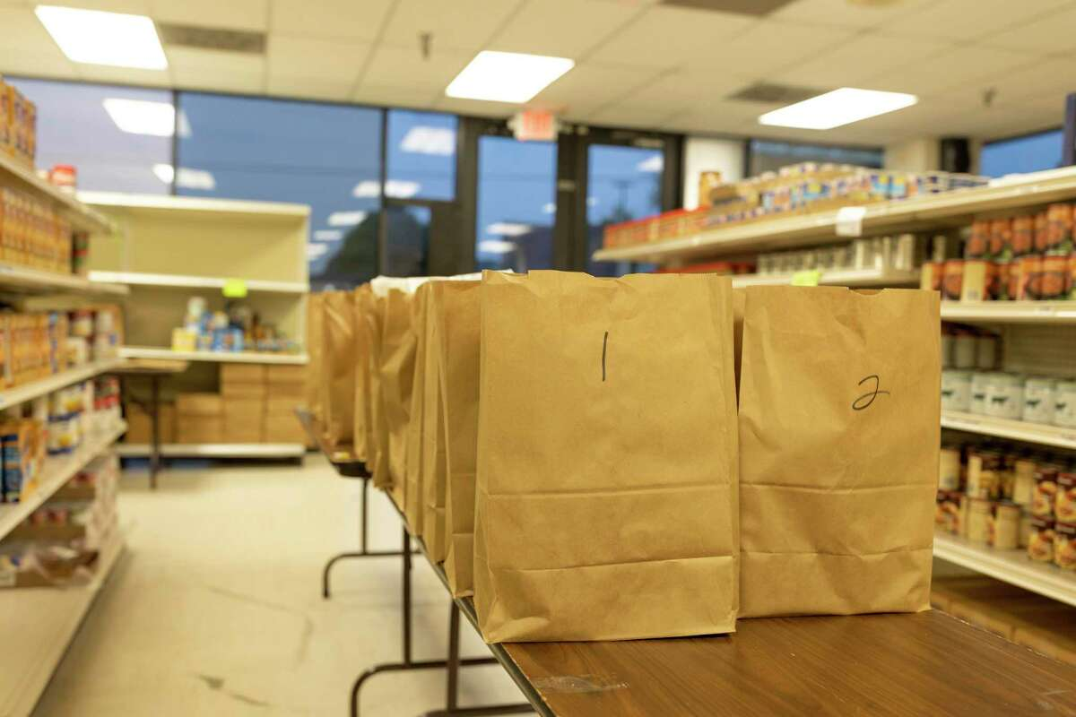 Paper bags of donated food rest on top of a table ready to be distributed at Northwest Assistance Ministries Watford Nutrition Center in Tomball, Friday, March 20, 2020. The food pantry has noticed a three times increase in families and residents seeking assistance since the new corona virus pandemic.