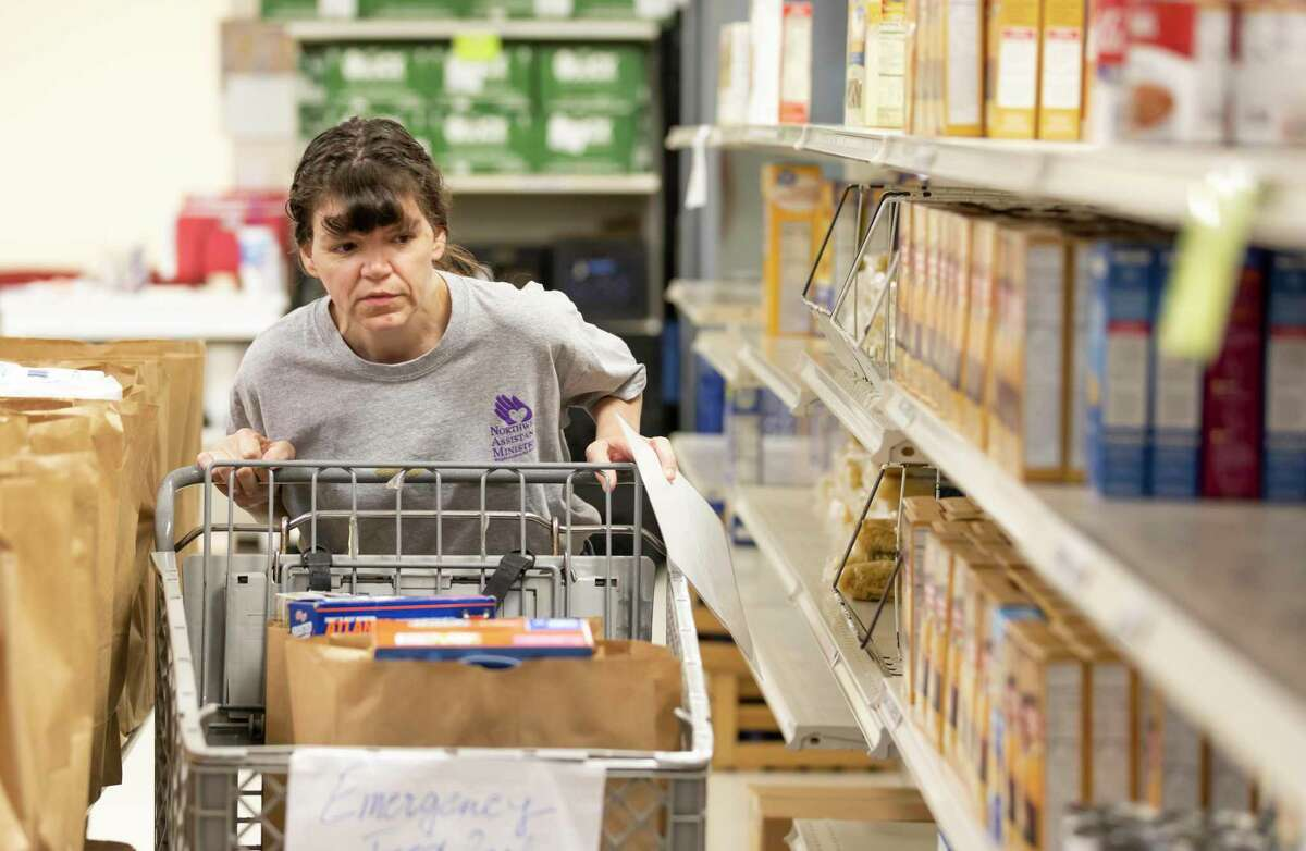 Northwest Assistance Ministries communications specialist, Shannel Vance, steers a cart down an aisle in the NAM's Watford Nutrition Center in Tomball, Friday, March 20, 2020. The food pantry has taken extra precautions in compliance with the Center of Disease Control and Preventions recommendations to stop the spread of COVID-19.