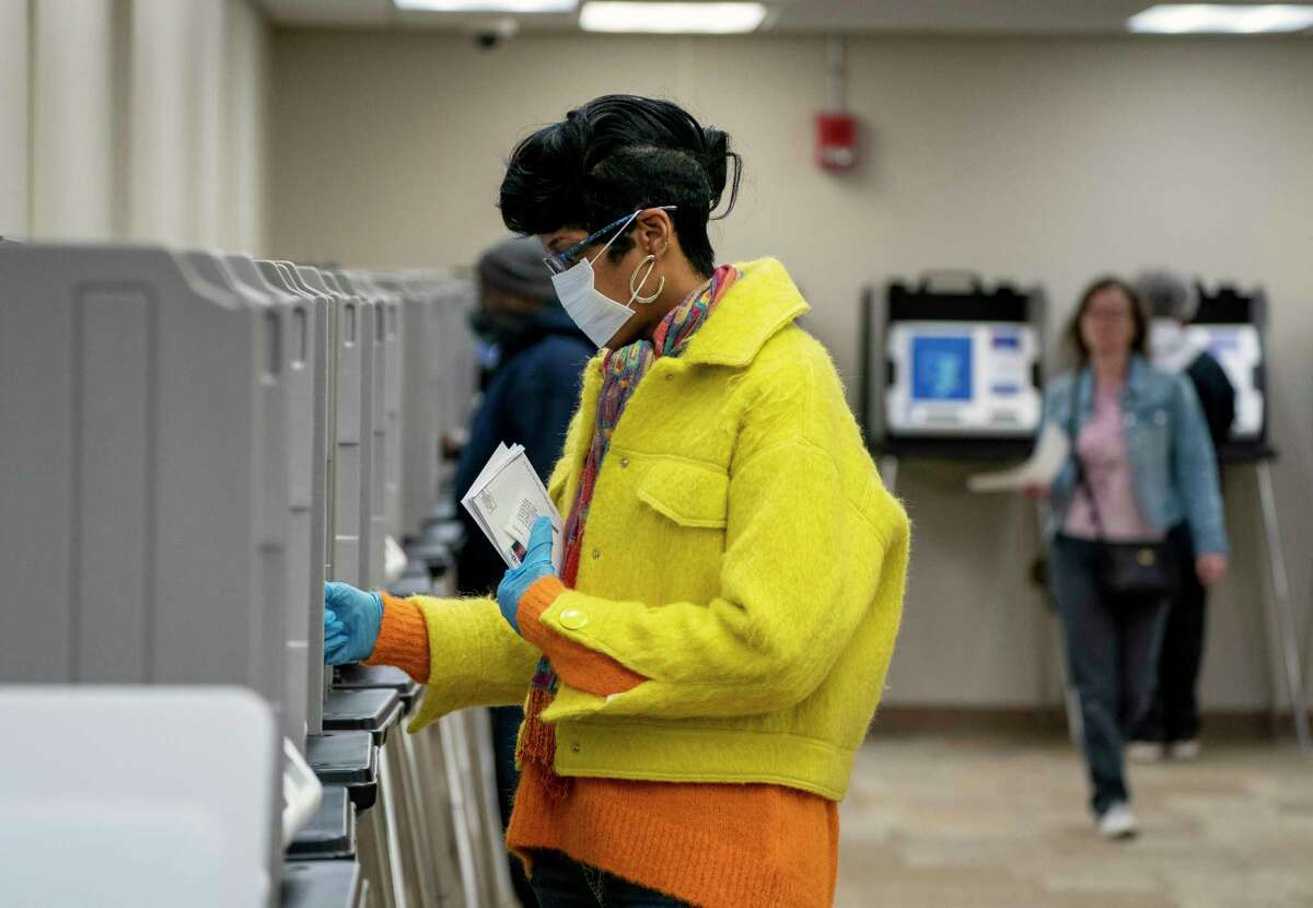 A masked and gloved voter casts her early ballot in Dayton, Ohio, on Monday, March 16, 2020, one day ahead of the state's presidential primary. Ohio's schools, restaurants and bars have been ordered closed to stop the spread of the coronavirus. (Kyle Grillot/The New York Times)