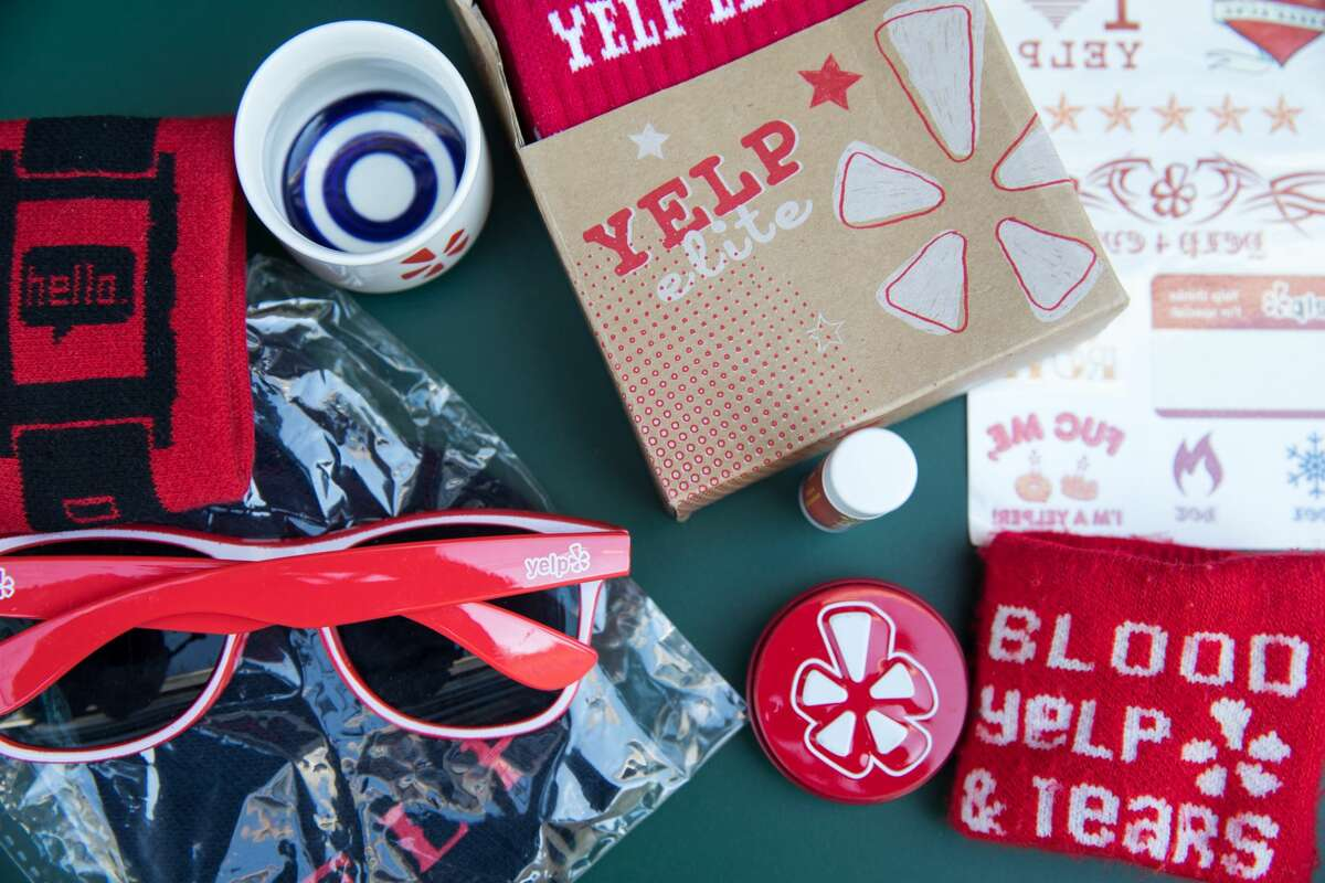 Ziyan C. and Ken Gwynn display some of the free swag they have received from attending Yelp Elite events. They include sunglasses, sweatbands, and shot glasses.