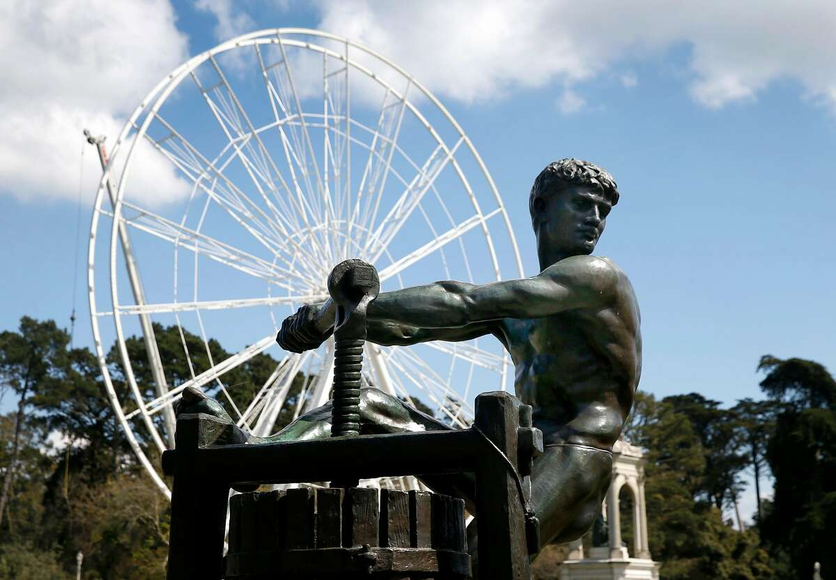 """The 150-foot high SkyStar Ferris wheel is assembled behind a sculpture displayed outside of the de Young Museum at Golden Gate Park in San Francisco, Calif. on Friday, March 20, 2020. The opening of the """"observation"""" wheel, erected to commemorate the 150th anniversary of the park, is being delayed due to the coronavirus pandemic."""