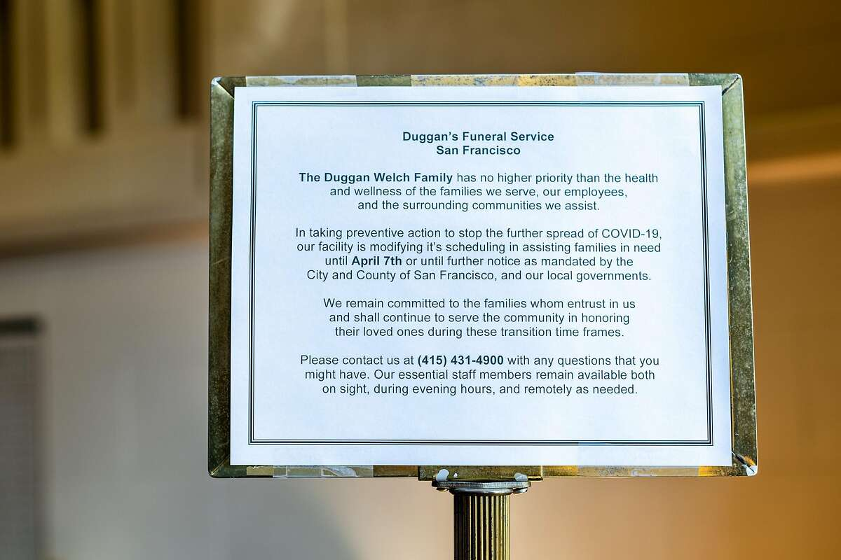 A sign about COVID-19 information at Duggan's Funeral Service on Friday, March 20, 2020, in San Francisco, Calif.