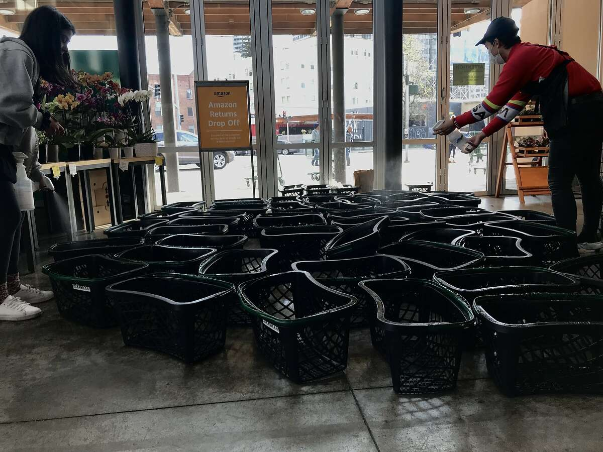 Whole Foods employees spray an anti-bacterial solution onto shopping baskets at Whole Foods Market in Oakland, Calif. on Friday, March 20, 2020. Since the Coronavirus outbreak, shoppers have taken more care to wear gloves, masks while maintaining social distance during their shopping experience.