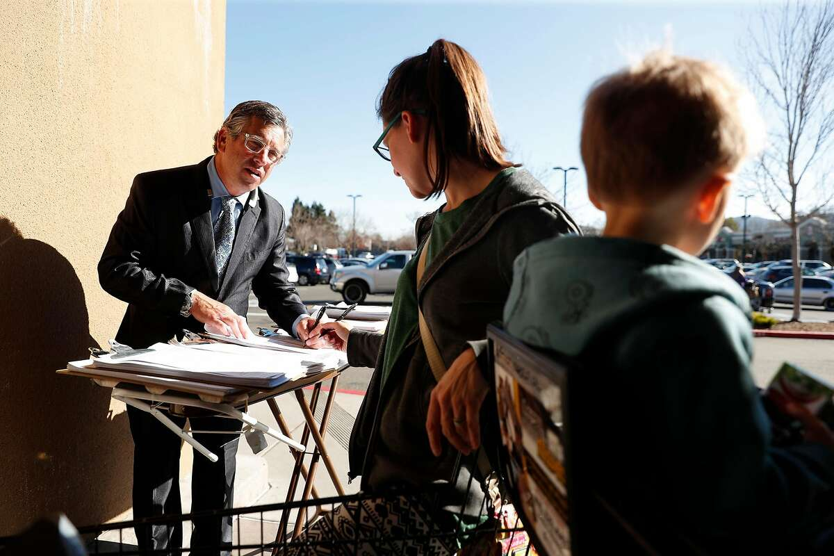 Kenn Zendels collects petition signatures from Kristi Hammer while her son, Lincoln, 2, waits outside of Safeway in Novato, Calif., on Wednesday, February 5, 2020.