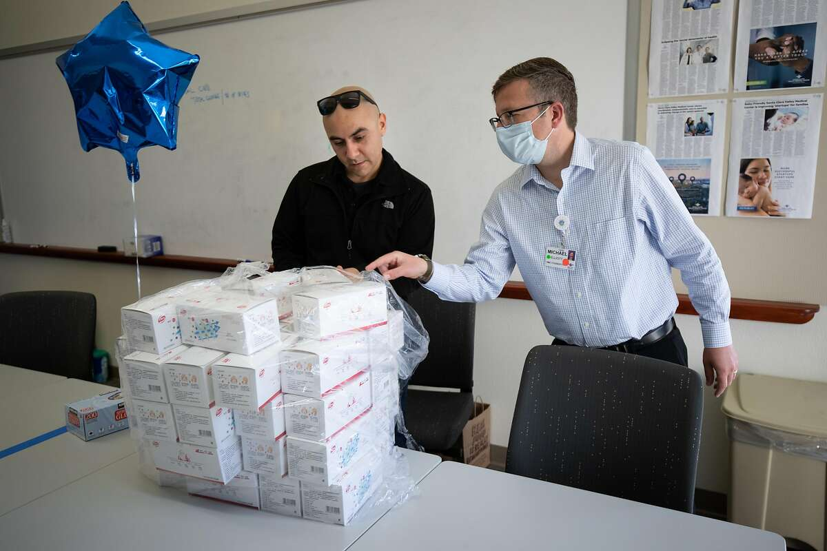 Ignacio Vallejo, at left, and Michael Elliott, COO of Valley Medical Center Foundation, sort through masks at Valley Medical Center Foundation Friday, March 20, 2020, in San Jose, Calif. The foundation is collecting masks and other protective equipment.
