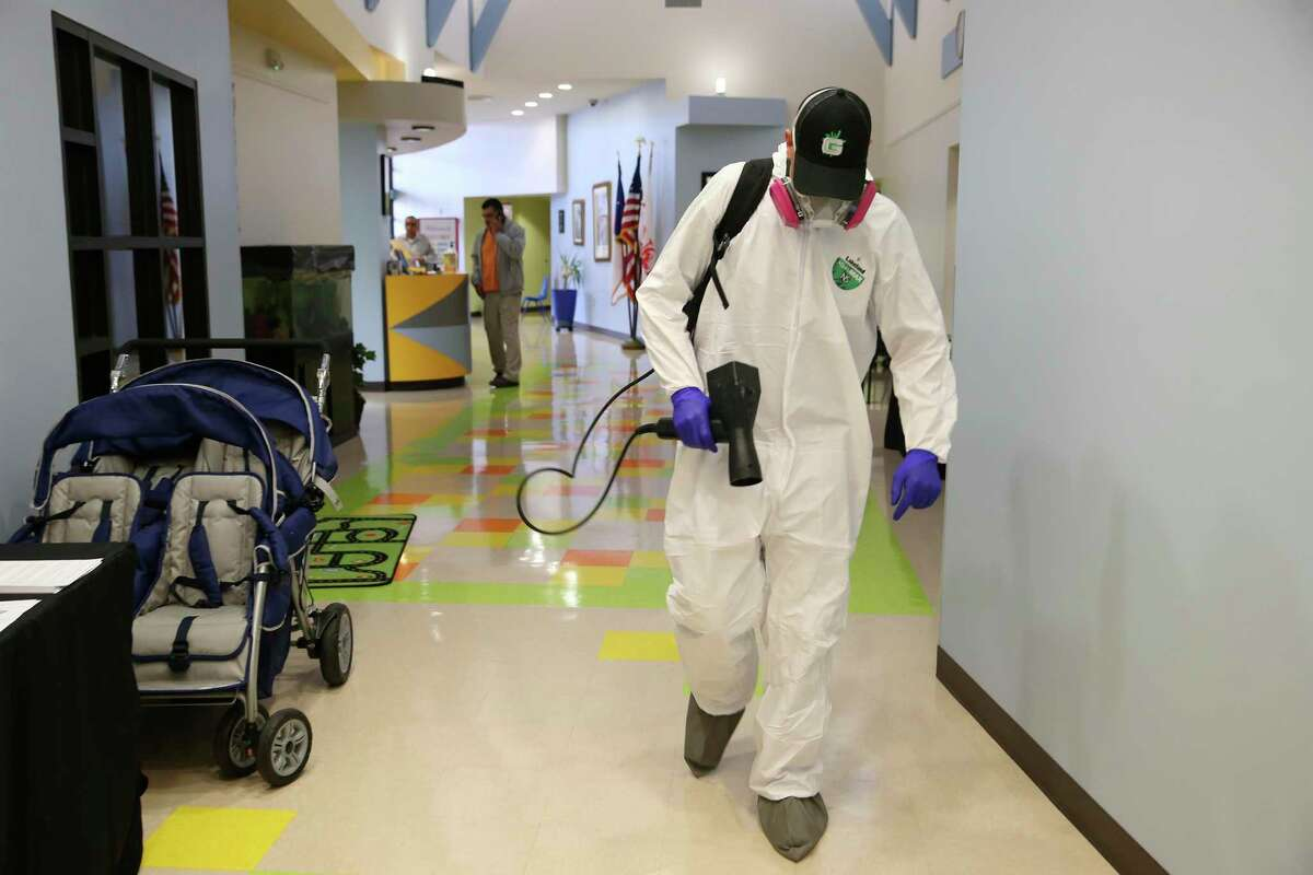Josh White, with Austin-based GermLogic, sterilizes the Carmen P. Cortez Avance Family Center on South San Jacinto Street on Friday. Disinfecting and cleaning companies such as GermLogic have seen a high demand for their services due to coronavirus concerns.