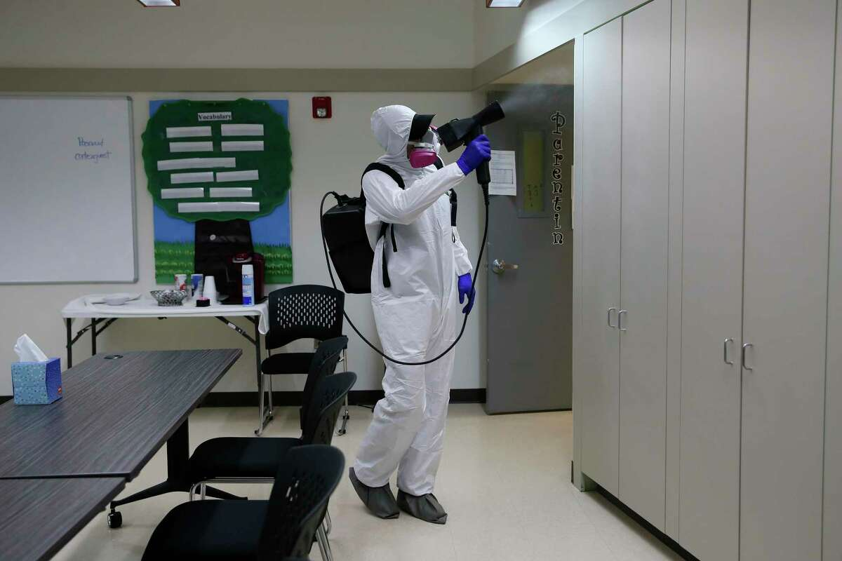 Josh White, with Austin-based GermLogic, sterilizes the Carmen P. Cortez Avance Family Center on South San Jacinto Street on Friday. Disinfecting and cleninag companies such as GermLogic have seen a high demand for their services due to coronavirus concerns.