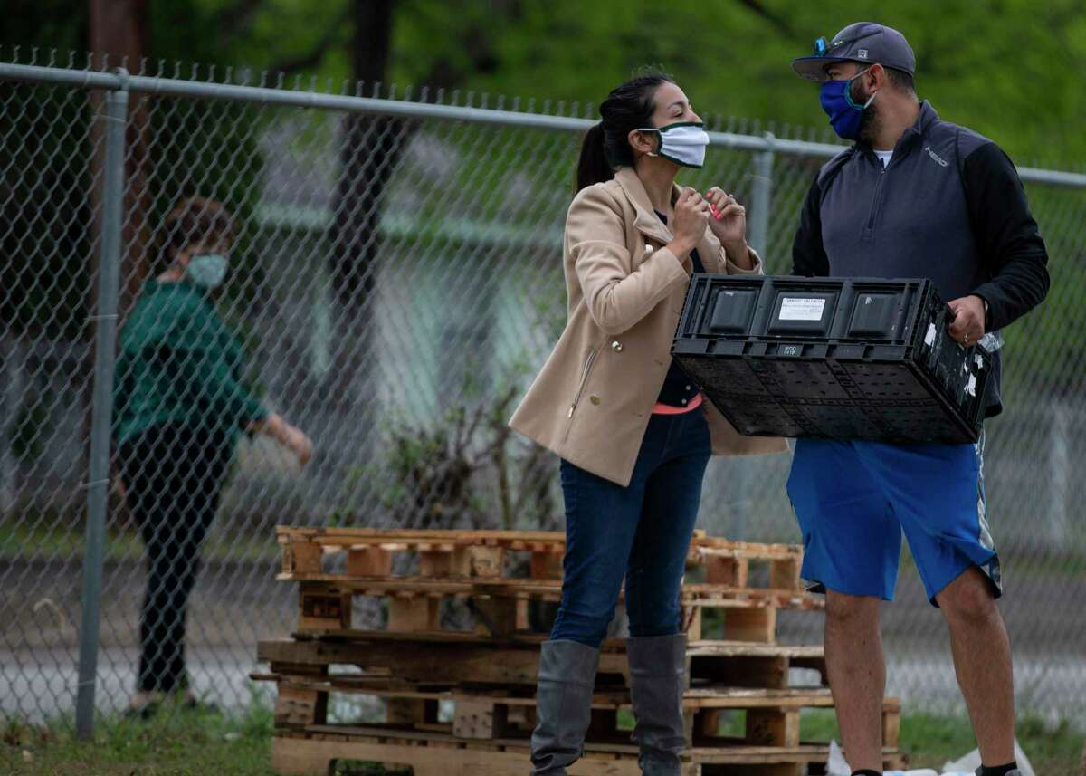 Chrystal Ramirez smiles at her husband, Robert Ramirez, as they volunteer at a food giveaway for at-risk families at the Edgewood Community Resource Center in San Antonio on March 20, 2020.