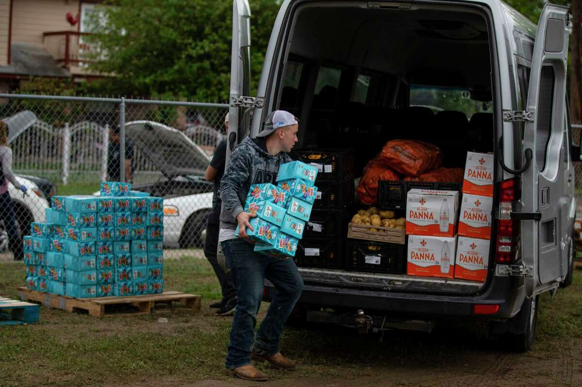 Davis Struk loads a van up with food during a food giveaway for at-risk families at the Edgewood Community Resource Center in San Antonio, Texas, on March 20, 2020.