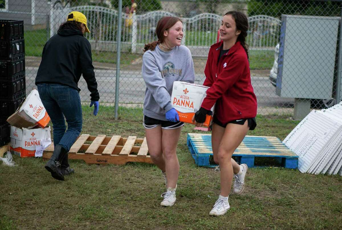 Norah Bridenbaugh, 16, left, and Hannah Cullum, 15, carry a box of water to a vehicle during a recent food giveaway in San Antonio.