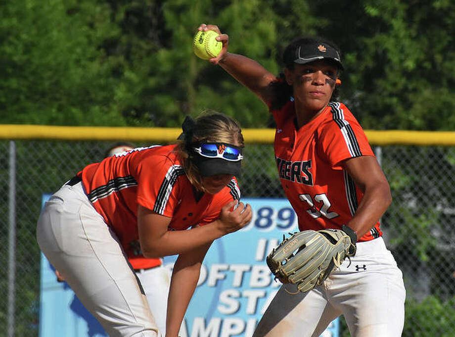 Edwardsville shortstop Maria Smith fires a throw across the diamond as third baseman Lexi Gorniak ducks out of the way.