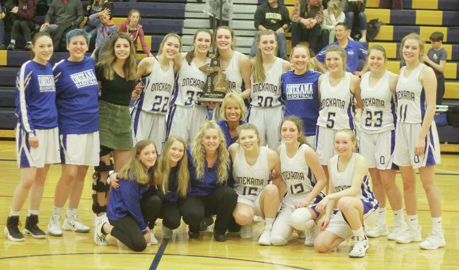 The Onekama girls basketball team poses with its Division 4 district championship trophy. (News Advocate file photo)