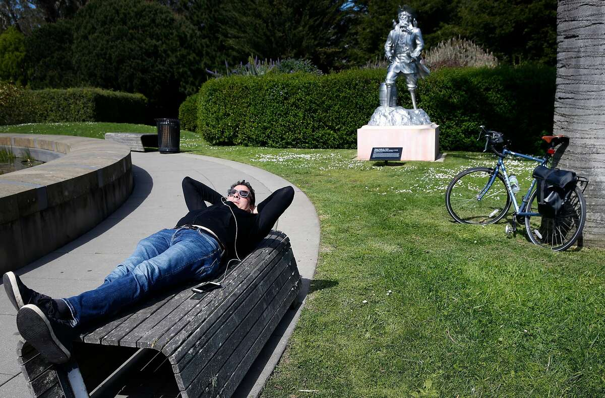 Josh Salafsky rests on a bench in the sculpture garden of the de Young Museum during a bike ride through Golden Gate Park as the coronavirus pandemic continues in San Francisco, Calif. on Friday, March 20, 2020.