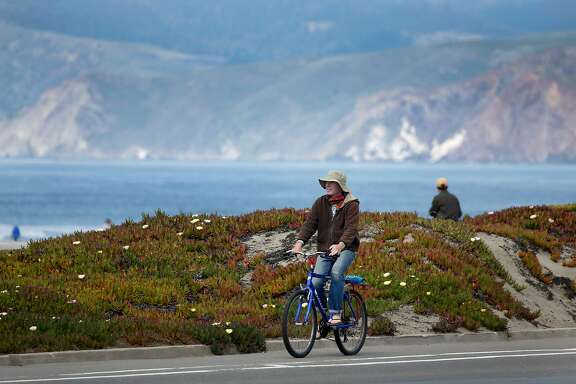 A bicyclist cruises down the Great Highway during the coronavirus pandemic in San Francisco, Calif. on Friday, March 20, 2020.