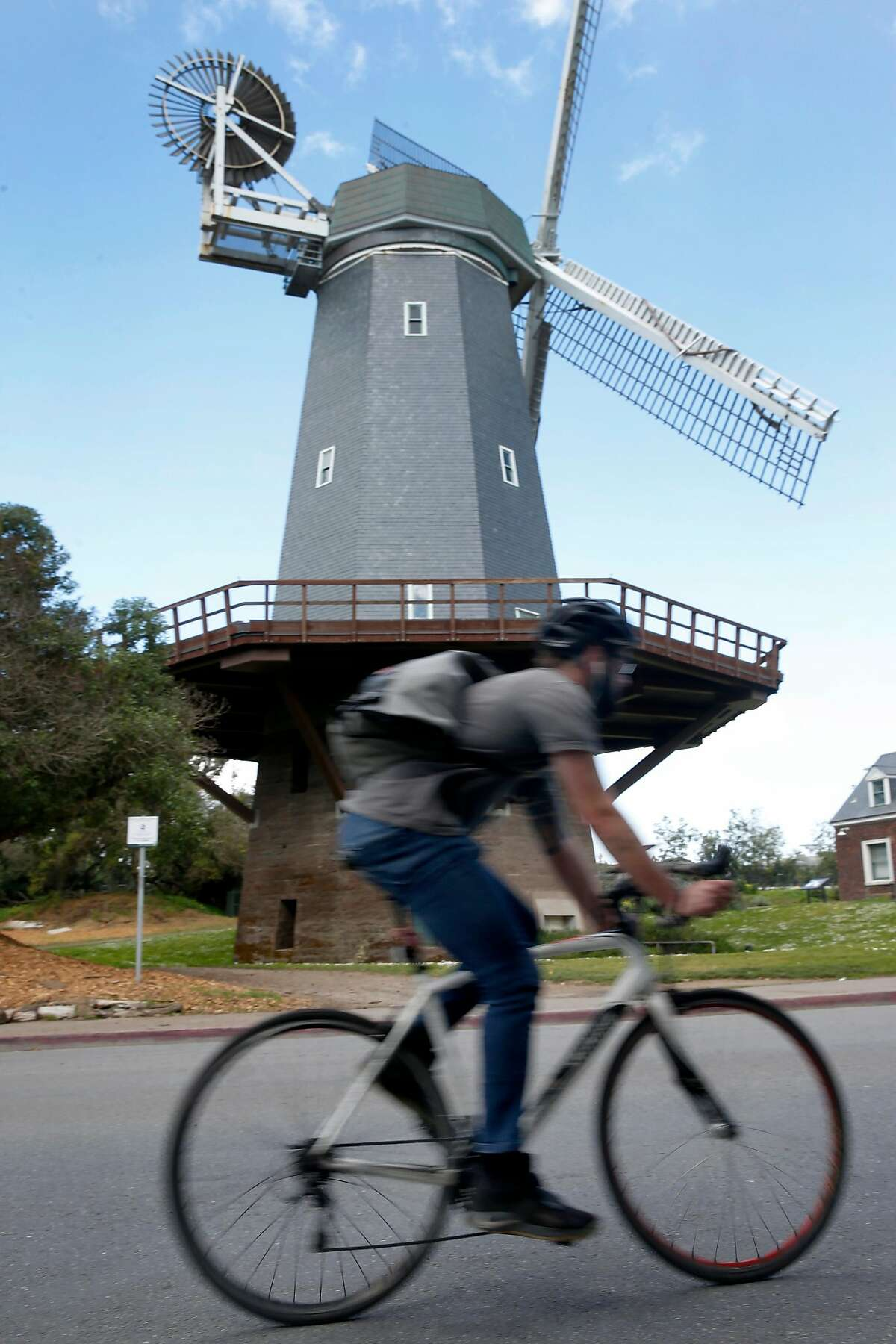 A bicyclist rides past the Murphy windmill in Golden Gate Park during the coronavirus pandemic in San Francisco, Calif. on Friday, March 20, 2020.