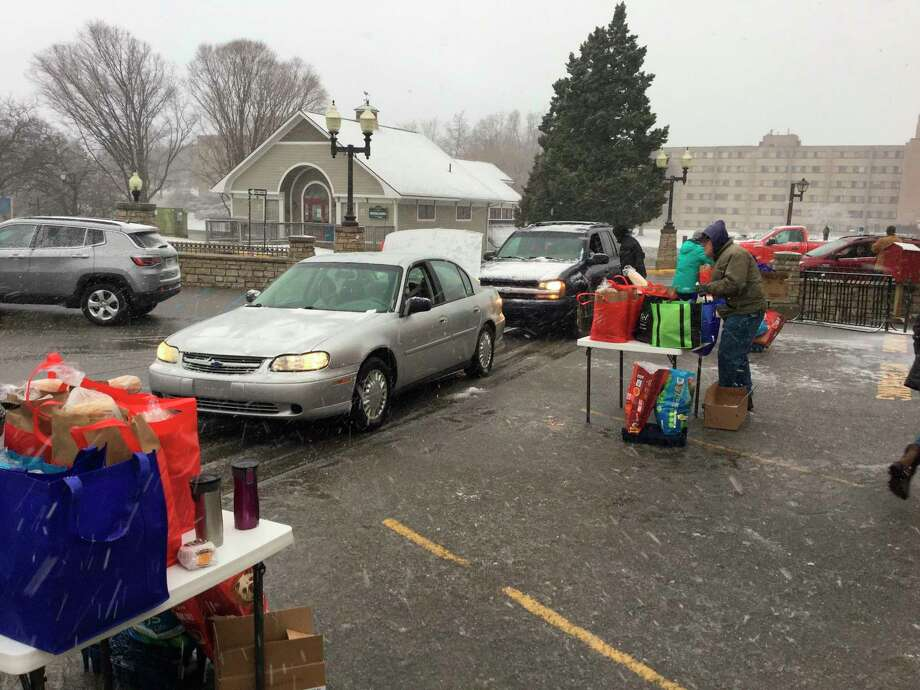 Elderly residents pull up to receive curbside service during this month's senior center food pantry. (Courtesy Photo)