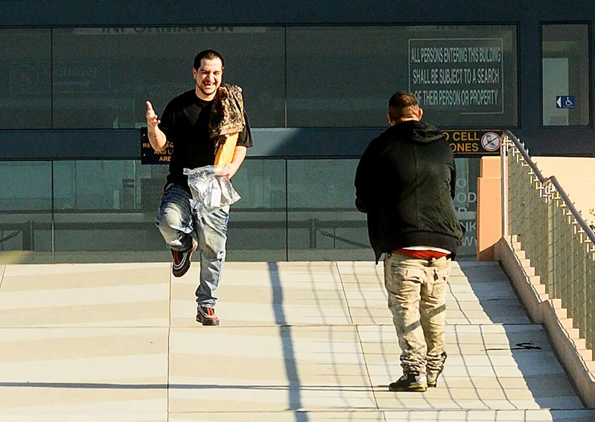 Florentino Pelayo celebrates as he leaves Santa Rita jail on Friday, March 20, 2020, in Dublin, Calif. At right is Simon Fajardo. The two men were among several hundred prisoners granted early release as the county tries to prevent coronavirus spread in a vulnerable population.