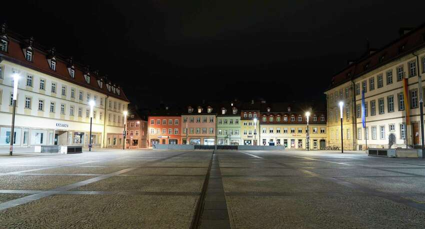 The deserted Maximiliansplatz is seen in the city center of Bamberg, Germany, shortly after midnight, early Saturday morning, March 21, 2020. A curfew went into effect for Bavaria. Leaving one's own home is now only allowed if there are good reasons. (Nicolas Armer/dpa via AP)