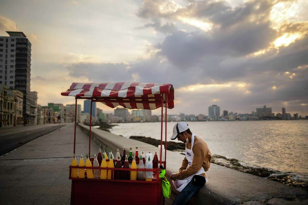 A slushy street vendor, who uses a protective face mask when he has customers as a precaution against the spread of the new coronavirus, waits for them along the seawall, normally bustling with pedestrians, in Havana, Cuba, Friday, March 20, 2020.